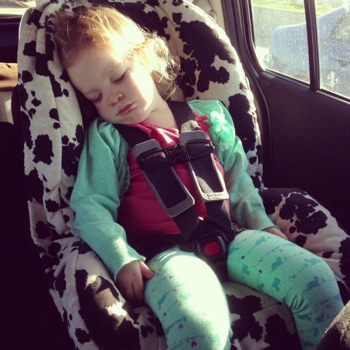 A young girl asleep in a child's car seat