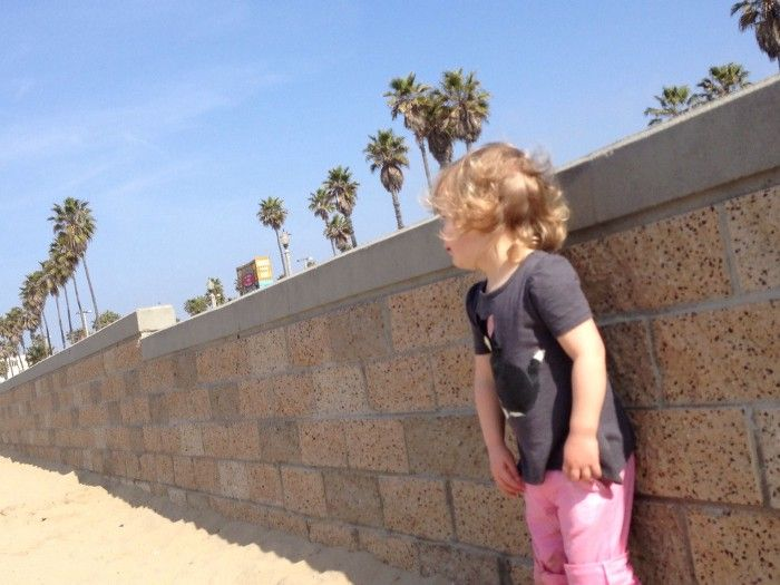 A young girl stands against a seawall at a California beach, with palm trees in the background.