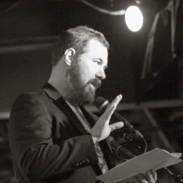 The author, under stage lights, speaks into a microphone